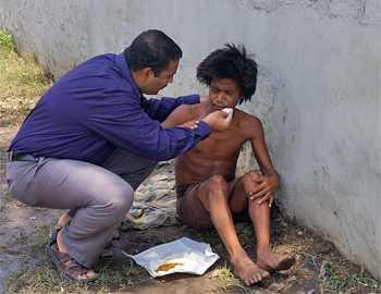 N Krishnan feeds a mentally ill person on a Madurai street